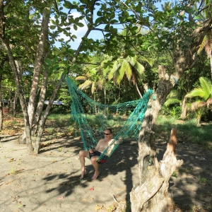 "Jim relaxing on a fishing-net ""hammock"" someone strung up on the beach."
