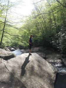 Karen on a boulder in the middle of a river, hiking with Megan in the Blue Ridge Mountains
