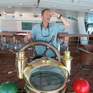 Jim was able to take the false helm in the top-floor cocktail lounge of our cruise boat.