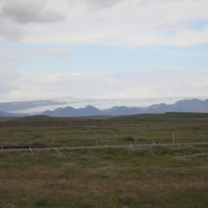 View of the Glacier Langjökull beyond the mountains and fading into the horizon