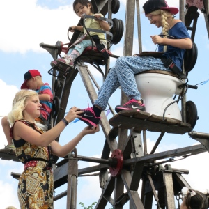 While the children rode around, a ferris wheel attendant playfully tried to steal shoes, hats, or anything she could reach from the children.