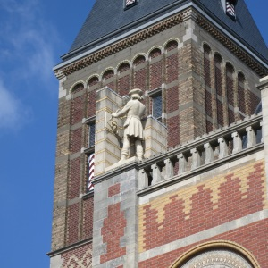 Statue of an artist working on the enormous art museum, Rijksmuseum.