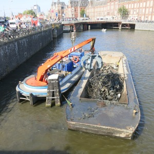 Canal cleaning. The orange machine digs into the water and picks up bicycles that were thrown over. While we watched, they scooped out about 8 mangled bicycles.