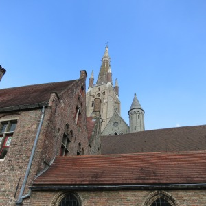 One of the beautiful spires in Bruges peaks over closer rooflines.