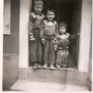 Jim and his brothers standing in the front door of their French house. Jim's in the middle.