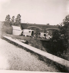 A picture taken by Jim's mom in 1952 of a Roma camp in front of a bridge.