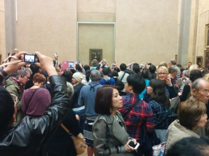 With her dark hair and enigmatic smile, this woman moves through a crowd focused on some famous painting.
