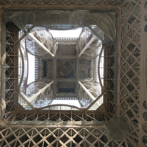Looking up the center of the Eiffel Tower from underneath.