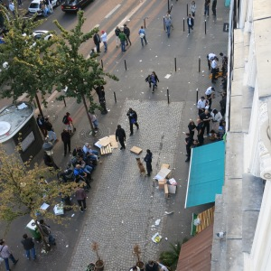 Police raiding the black market. Note the officer with the dog and the line of men detained up against the wall on the right. Also notice how the large crowd is gone!