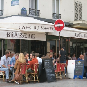 Parisians love to eat outside. Sidewalk seating is often full with people enjoying a leisurely meal or cup of coffee. Note the graffiti on the do-not-enter sign.