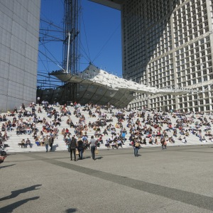 Business lunch crowd on the steps of La Défense arch. The parabolic object in the center is a wind deflector.