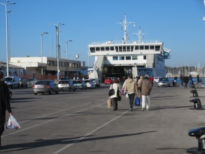 Boarding a ferry to visit a nearby island. Cars and pedestrians all come in and out together.