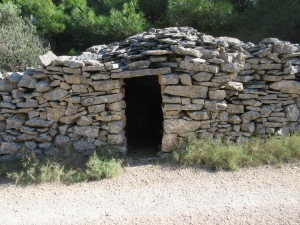 A small round stone hut built into a wall. The exact use of these ancient constructions is unknown. Today they are used by farmers for storage.
