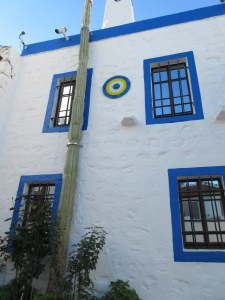A typical Bodrum house with blue trim, white walls, and protection from the evil eye. Note the extremely tall cactus!