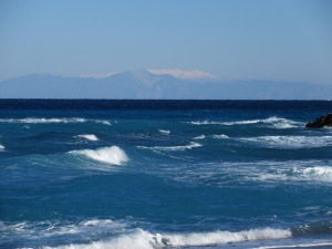 A stormy day at a Rhodes beach with snow on the Turkish mountains.