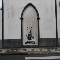 Some Banksy-inspired graffiti in the Azores, above characteristic black and white mosaic sidewalks.